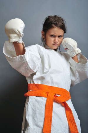 Little girl in martial arts unifor doing karate photo