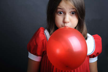 Little girl blowing a red balloon, close up portrait photo