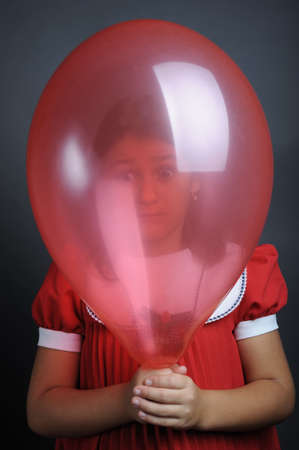 Little girl looking through a red balloon, close up portrait photo