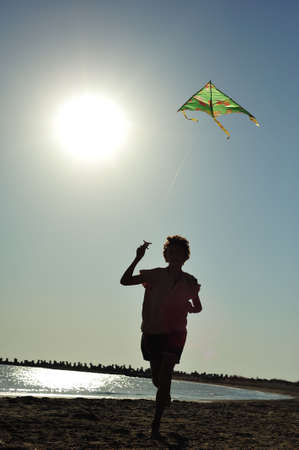 Boy running and flying a kite photo