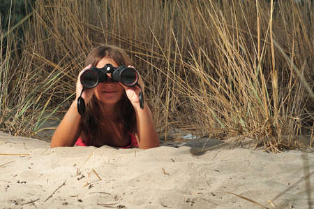 spies: Young girl looking through binocular, low angle view Stock Photo