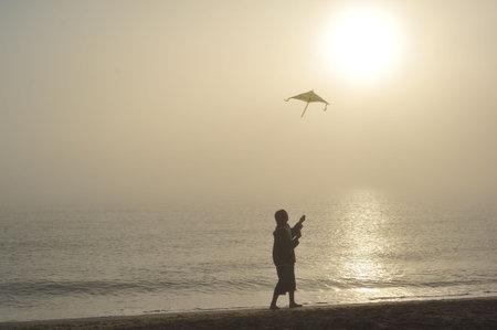 Boy flying a kite on beach at sunrise photo