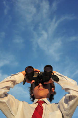 Young business man looking through binocular, low angle view photo