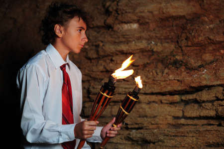 Young businessman lighting with torch in a cave photo