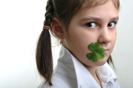 Little girl holding a clover in corner of her mouth photo