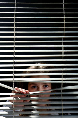 blinds: Girl looking through blinds window Stock Photo