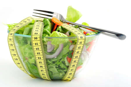 Conceptual assorted salad and tape measurement, close up