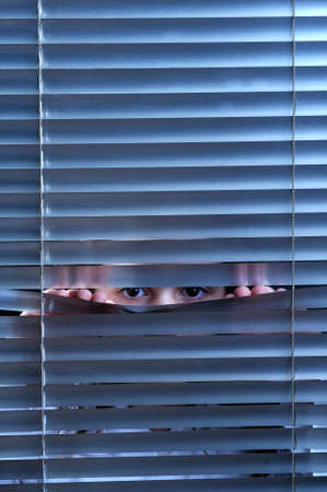 Girl's eyes looking through window blinds Stock Photo - 4494230