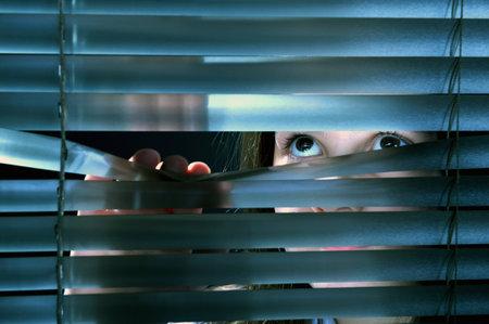 stores: Girl's yeux en regardant � travers la fen�tre de stores