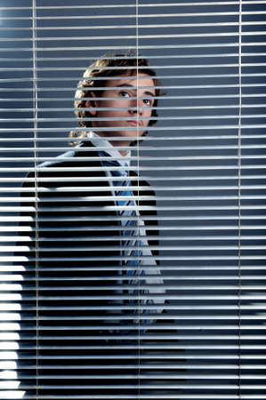 Young businessman behind a window blinds looking up photo