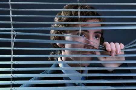Young businessman looking through window blinds photo