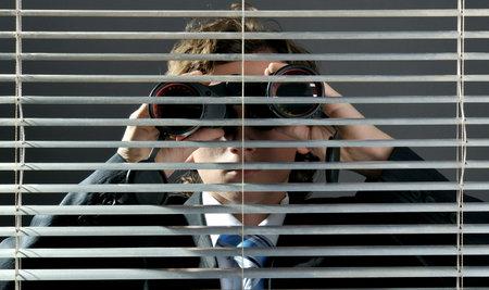 oversee: Businessman looking through binoculars behind a blinds window