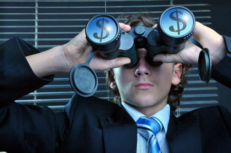 proceeds: Young businessman looking through binoculars, dollar sign reflected on lens Stock Photo