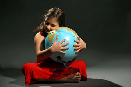 Little girl in red dress embracing Earth globe photo