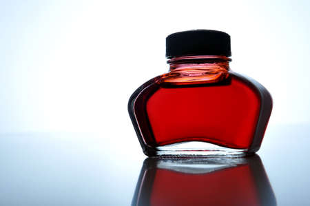 Red ink bottle on table, close up photo