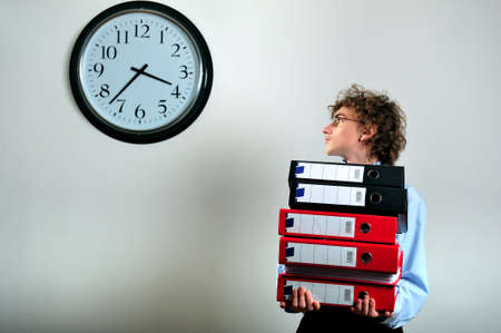 Young businessman holding stack of folders and looking at clock Stock Photo - 4494163