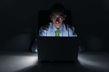 late: Businessman working at computer laptop in night