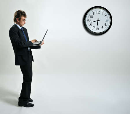 Young businessman standing up and using laptop, free space photo