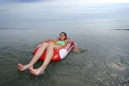 Little girl sitting on inflatable boat on sea Stock Photo