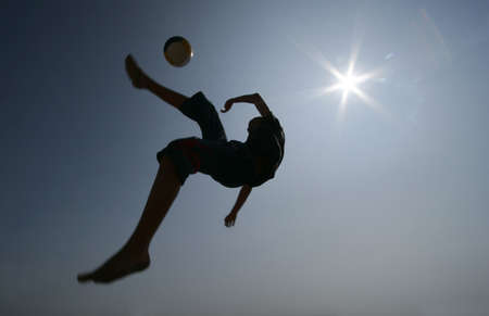 Silhouette of boy playing football backlighting by sun photo
