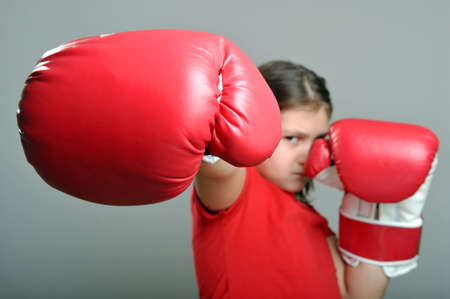 Young girl wearing boxing gloves and punching