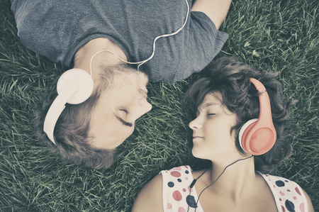 Couple listening to music on headphones Foto de archivo