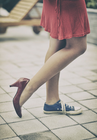 Woman legs in different shoes