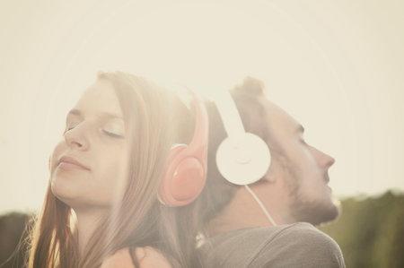 Boy and girll listening to music on headphones Standard-Bild