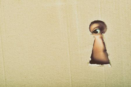 段ボールに概念的な鍵穴を通して見る目は、クローズ アップ