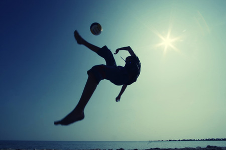 Young boy playing football - low angle view