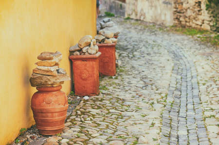 Decorative pottery on a cobblestone street in the city of Sighisoara, Transylvania, Romania Stok Fotoğraf - 82887394