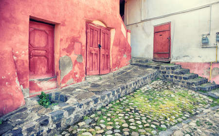 Small street paved and a house with pink walls in the city of Sighisoara, Romania, Transylvania Stok Fotoğraf
