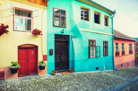 市のシギショアラ、ルーマニア、トランシルヴァニア地方の舗装道路を禁止するための花と古い家