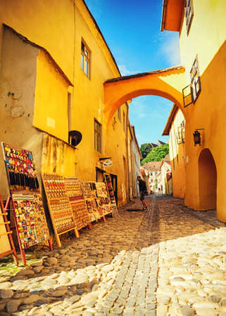 Small street paved and selling souvenirs near Dracula's house in the city of Sighisoara, Romania, Transylvania Stok Fotoğraf - 82887203