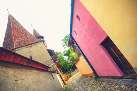 Small street paved and a house with pink walls in the city of Sighisoara, Romania, Transylvania Stock Photo