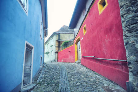 Small street paved and a house with blue and pink walls in the city of Sighisoara, Romania, Transylvania