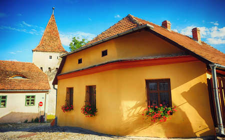 Old house with flowers at windows and cobblestone streets, castle Sighisoara, Romania, Transylvania Stok Fotoğraf - 82886940
