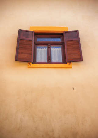 Windows with wooden shutters open site; a brown wall, castle of Sighisoara, Transylvania, Romania Stock Photo