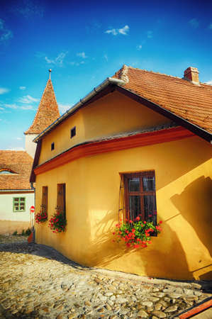 Old house with flowers at windows and cobblestone streets, castle Sighisoara, Romania, Transylvania Stok Fotoğraf - 82907500