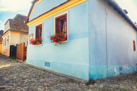Old house with flowers window on a paved street of the Fortress Sighisoara in Romania, Transylvania Editorial