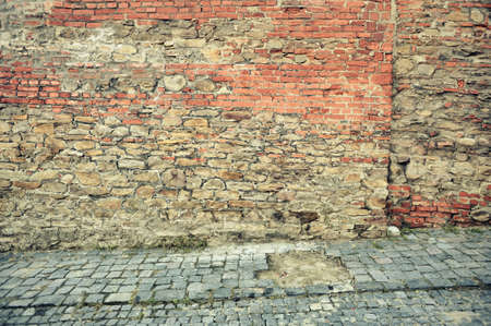 Old red brick wall on a paved street of the city