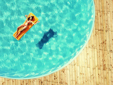 Young girl sitting on a beach mattress in the pool.. This is a 3d render illustration.