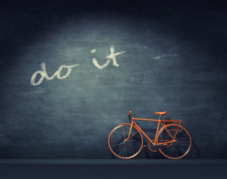 Orange bicycle leaning against a blackboard and message do it.  This is a 3d render illustration.