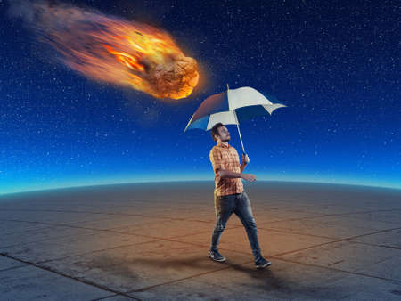 Man holds an umbrella while walking and a meteor falling down right behind him. The concept of careless man.