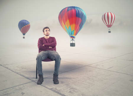 Man sitting on chair and looking at balloons.