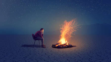 A thoughtful man in front of a campfire into the night .