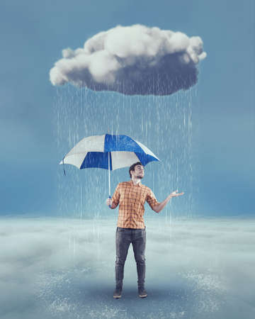 Young man holds an umbrella under a rainy cloud and checks if is still raining. Stok Fotoğraf - 96735102