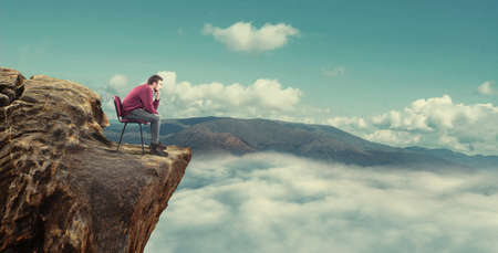 Thoughtful man sitting on chair at the top of the mountain and looking to horizon. Stock Photo