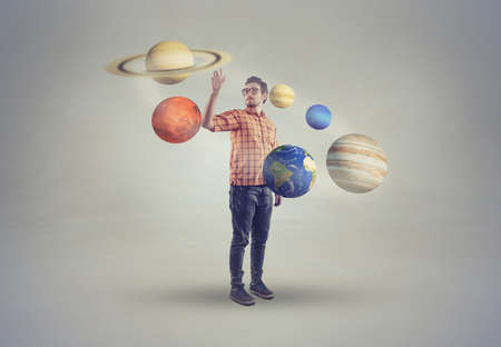 Young man in middle of solar system pointing to a planet