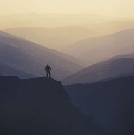 Sillouthe of a hiker on the top of a mountain admiring the landscape.